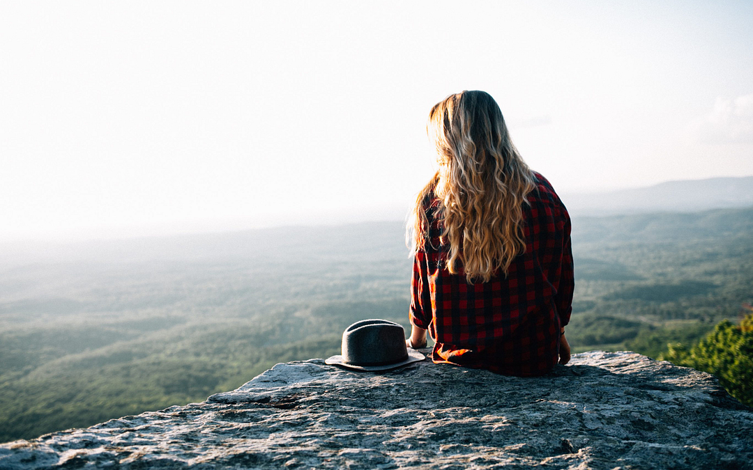 Young woman sitting on mountain top balancing estrogen